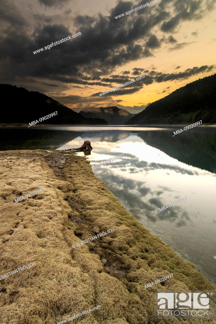Stock Photo: The Sylvenstein impounding reservoir at low tide during sunset.