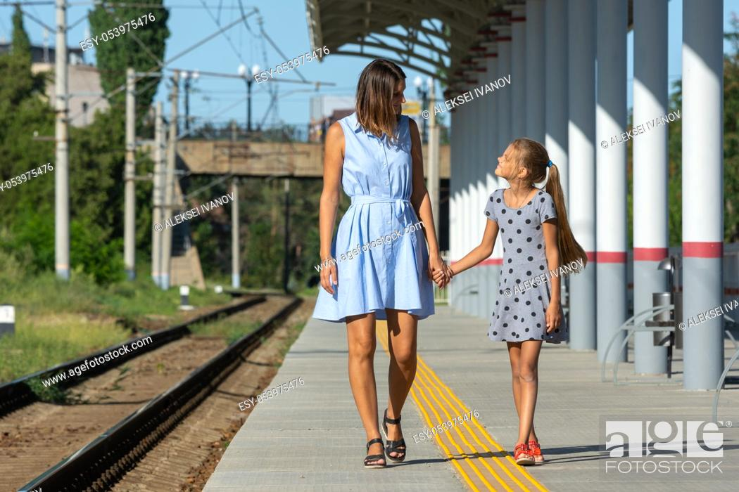 Photo de stock: Young beautiful girl and teenage daughter walk on the empty platform of the train station.