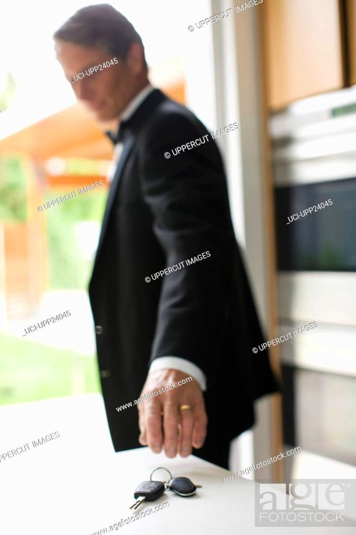 Stock Photo: Man in tuxedo reaching for keys on kitchen counter.