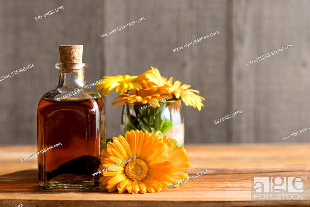 Stock Photo: A bottle of calendula (marigold) tincture with fresh calendula flowers on a wooden background.
