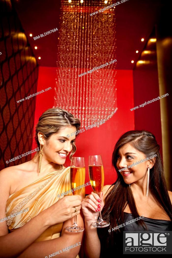 Imagen: Glamorous Hispanic women toasting with Champagne.
