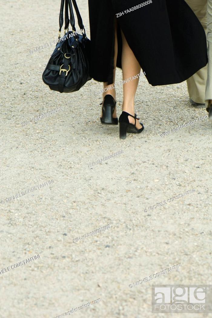 Stock Photo: Well-dressed couple walking away on gravel, cropped rear view.