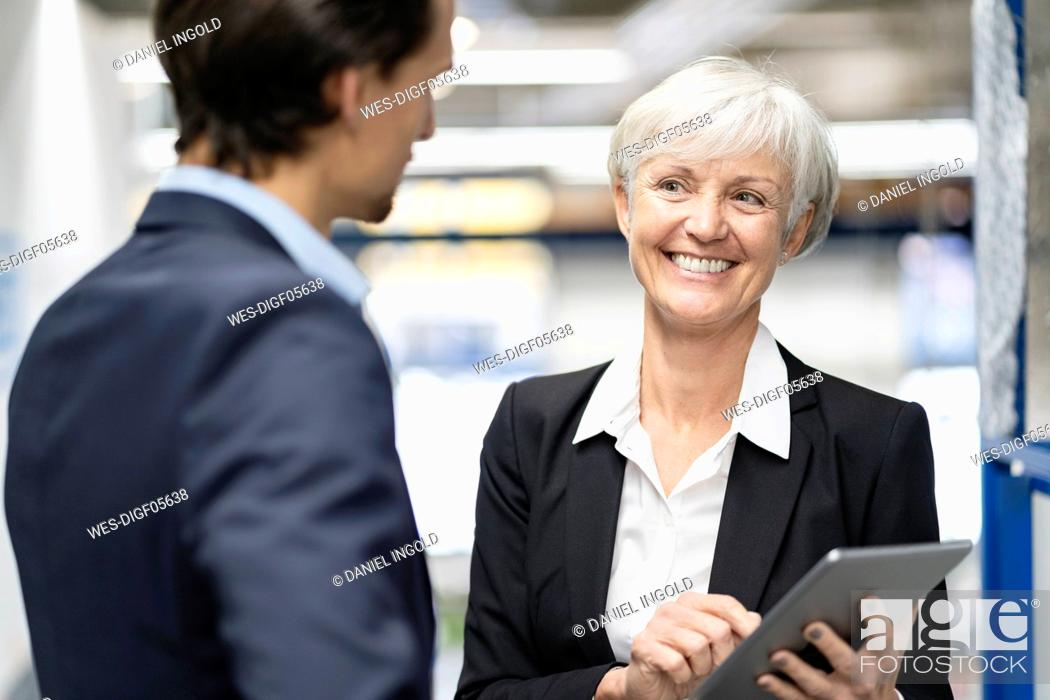 Stock Photo: Smiling businessman and senior businesswoman with tablet talking in a factory.