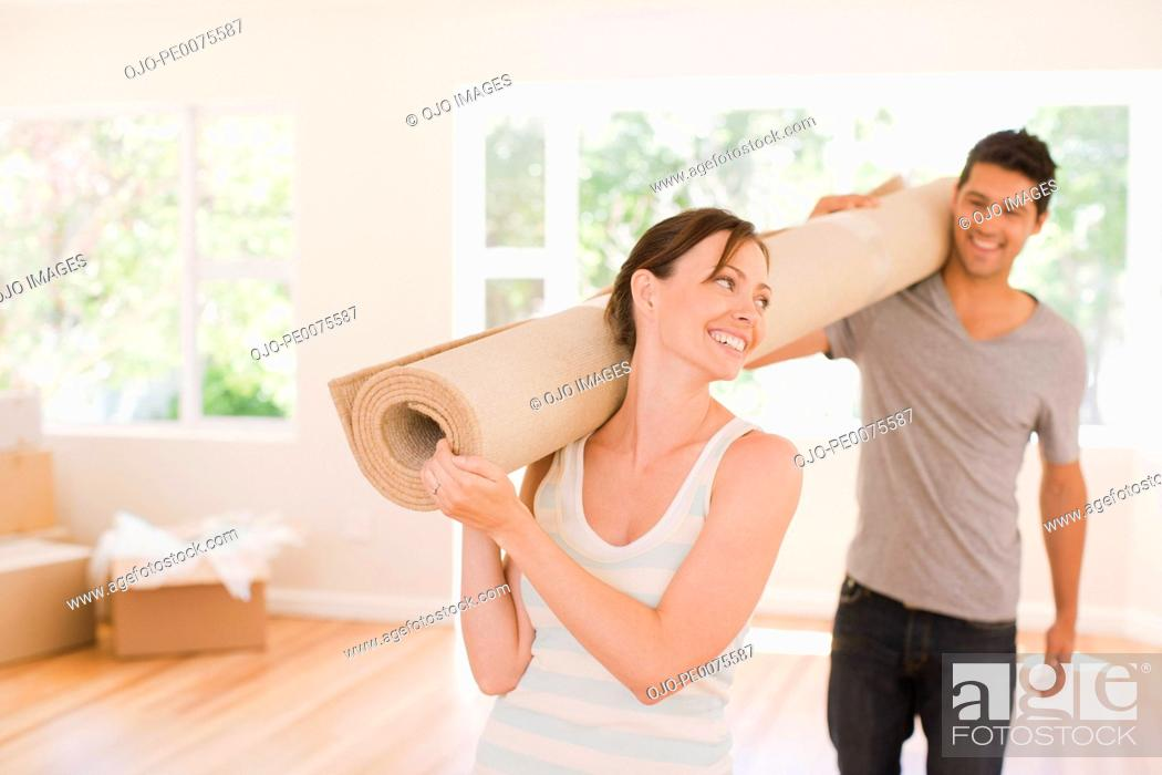 Stock Photo: Couple carrying carpet into new house.