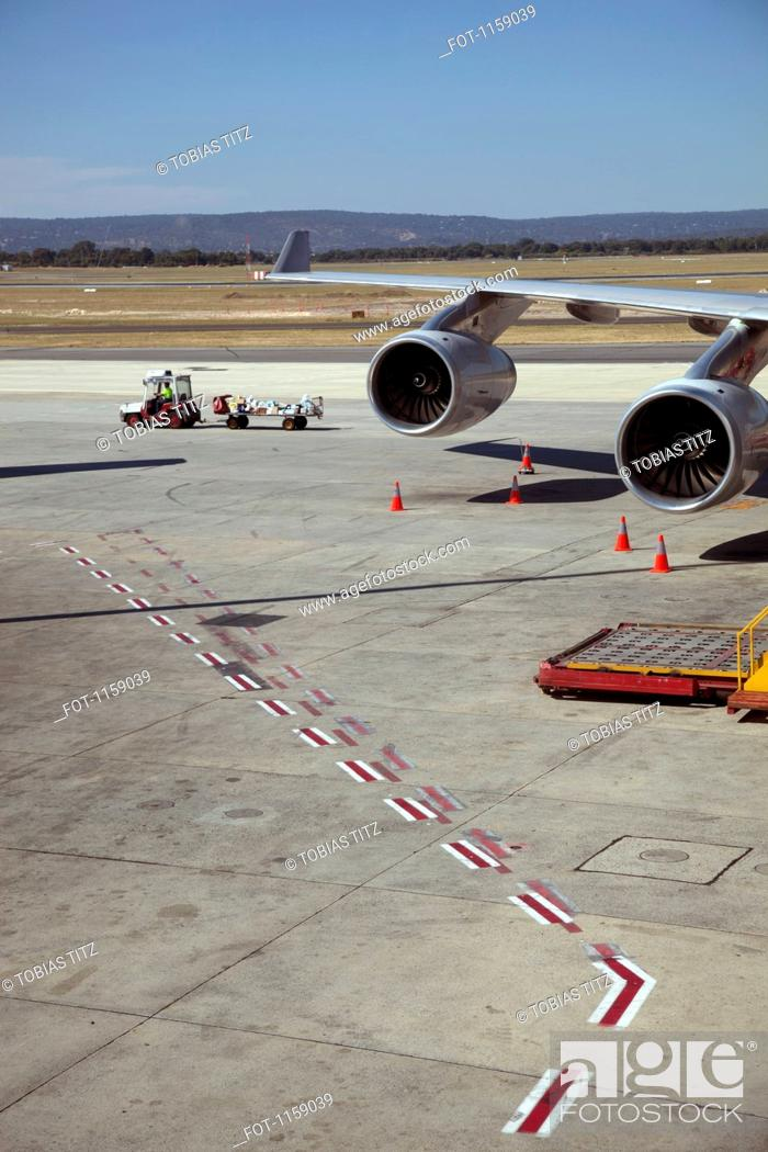 Stock Photo: Luggage trolley moving away from jet.