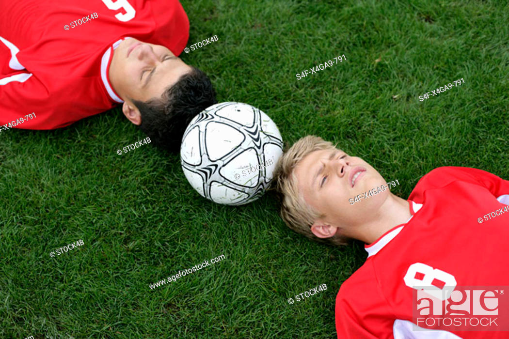 Stock Photo: Soccer player lying head to head on grass, football between them.