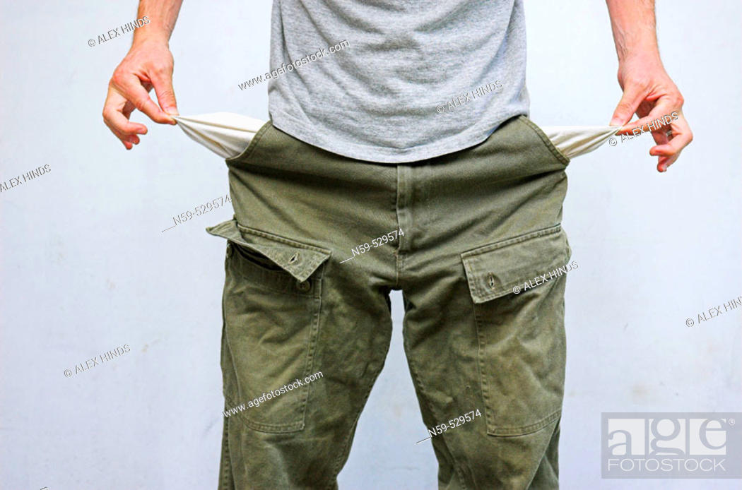 Stock Photo: Young man pulling his pockets out to illustrate lack of money.