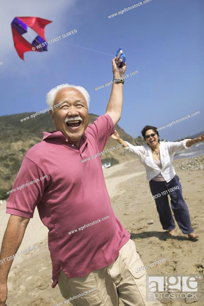 Stock Photo: Couple flying kite on Beach.