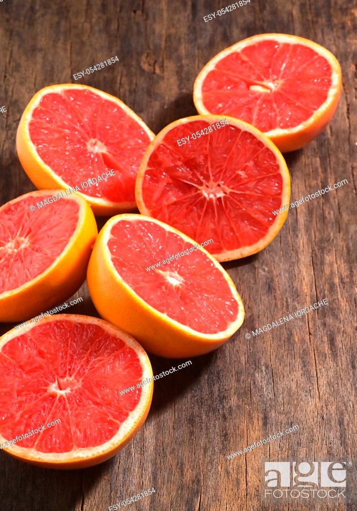 Stock Photo: Sliced Red Ripe Grapefruits On Wooden Table.