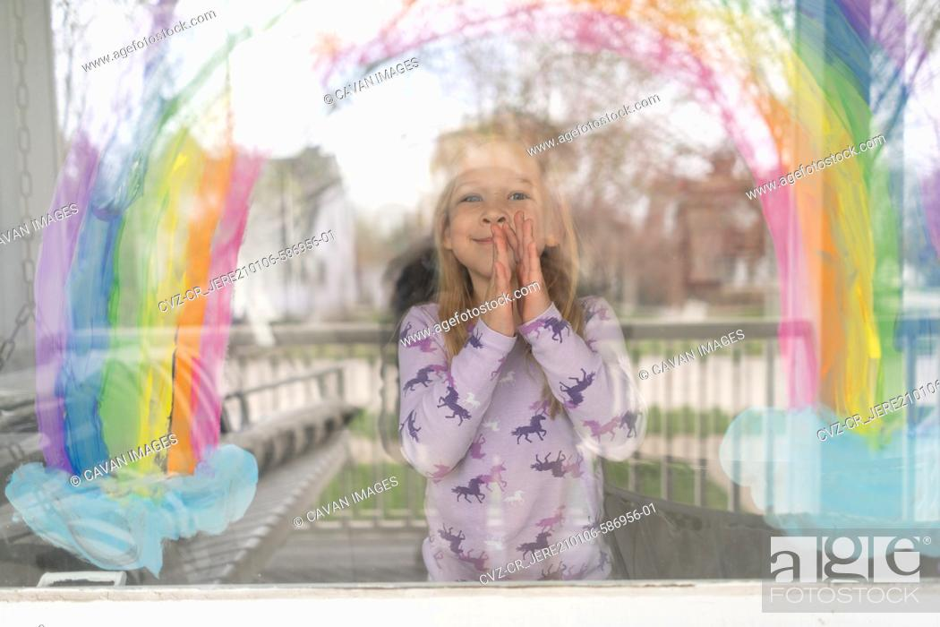 Stock Photo: outside in view of cute girl under rainbow painted on window.