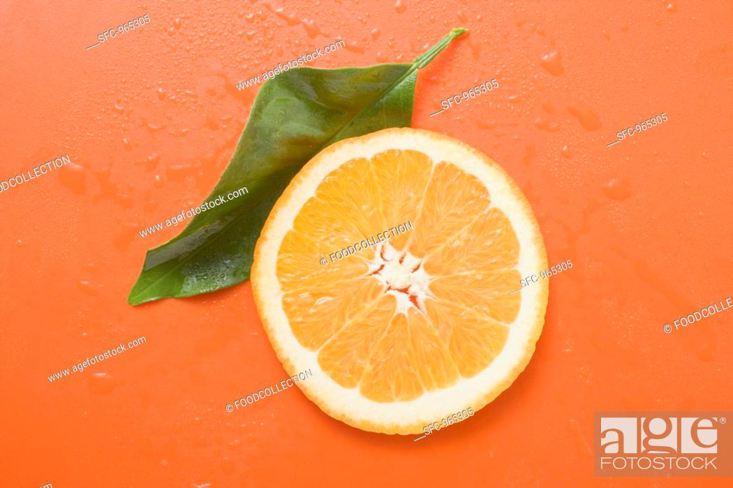 Stock Photo: Slice of orange and leaf with drops of water.