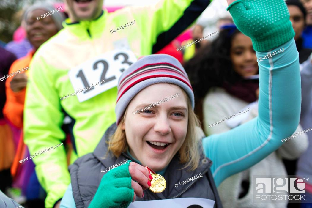 Stock Photo: Enthusiastic woman with medal cheering at charity race.