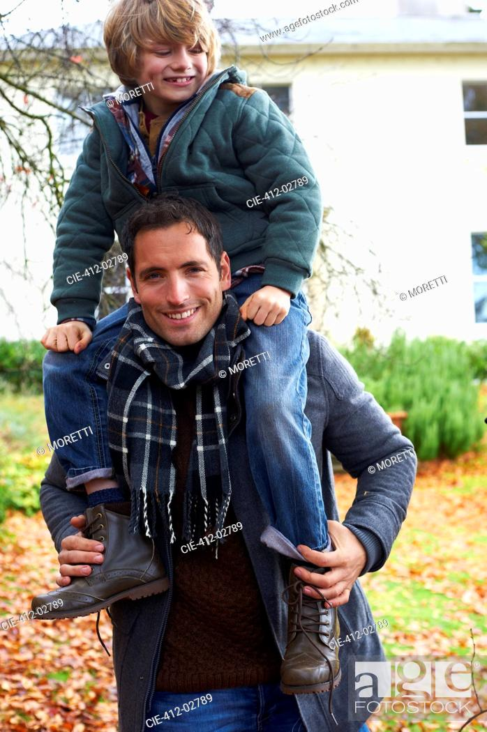 Stock Photo: Father carrying son on shoulders outdoors.