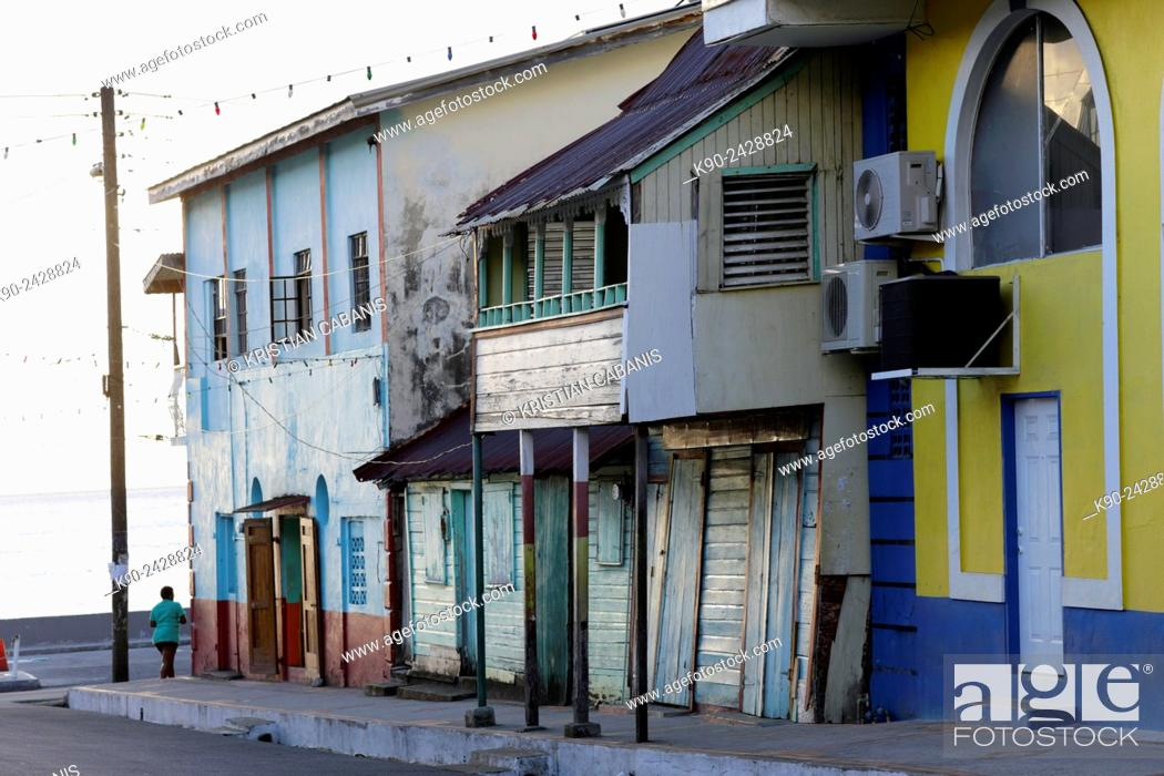 Stock Photo: Streetscene with wooden houses in the center of Soufrière and a woman just turning around the corner, St Lucia, Windward Islands, Lesser Antilles.
