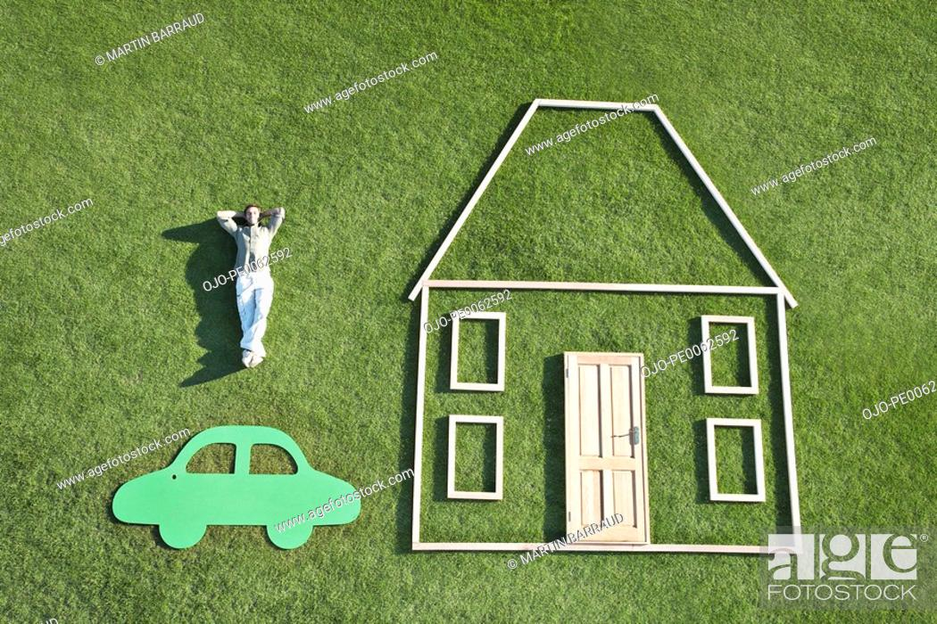 Stock Photo: Man laying on grass next to outline of house and car.