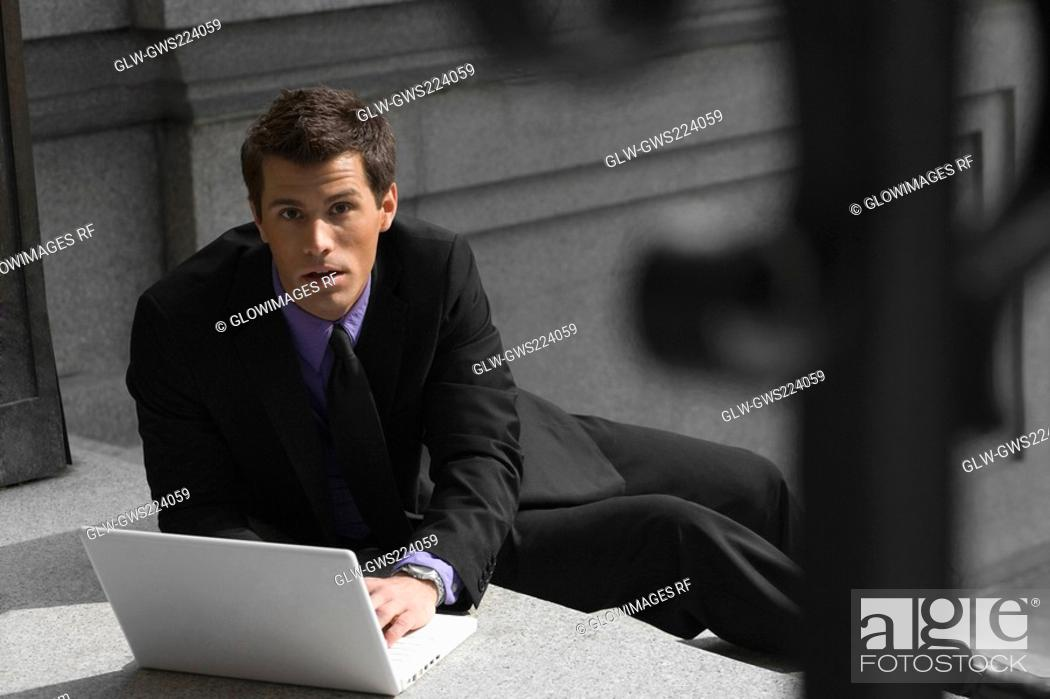 Stock Photo: Portrait of a businessman sitting on steps and using a laptop.