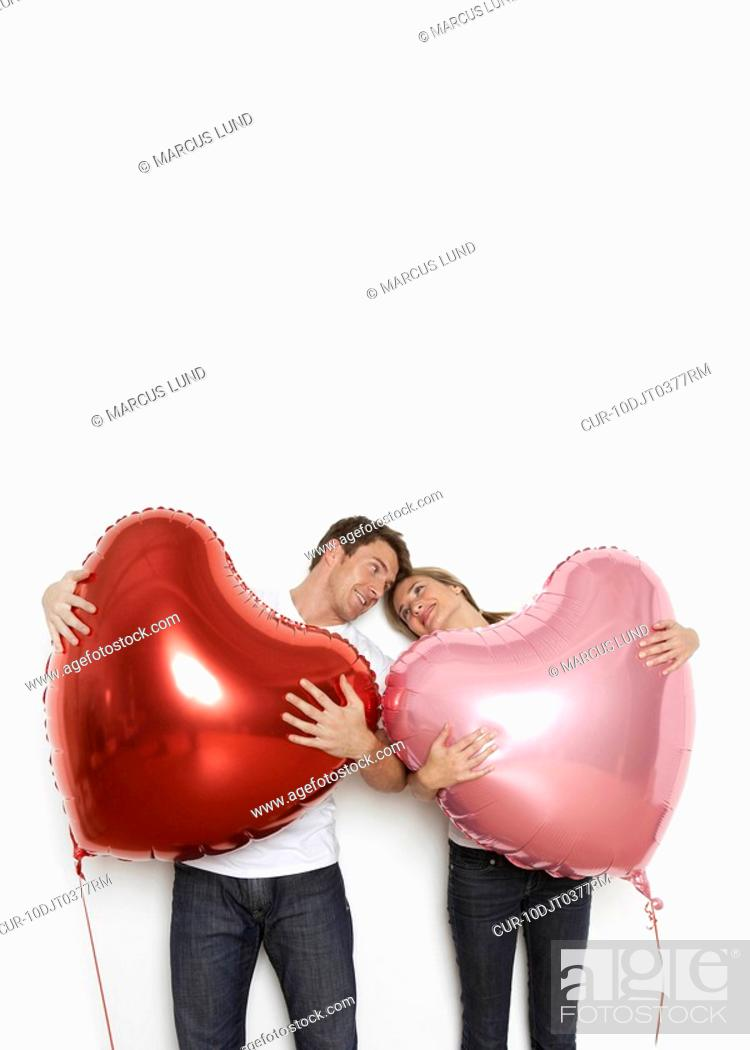 Stock Photo: Young couple holding huge heart shaped balloons and looking at each other lovingly.