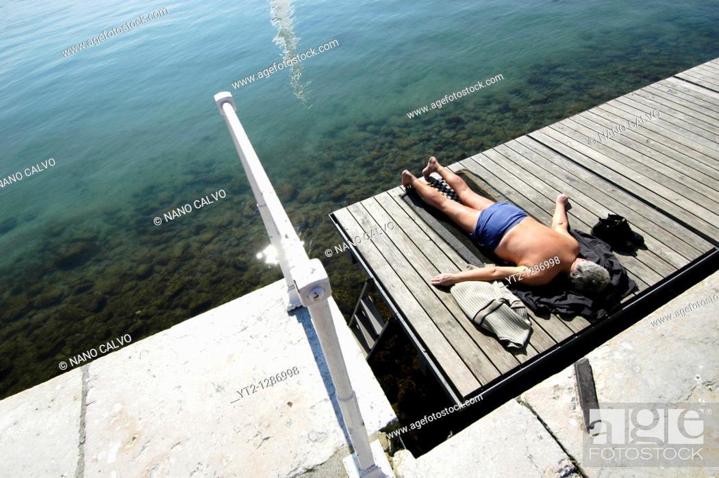 Stock Photo: An elderly man taking a sunbath in Bains des Paquis, in Geneva, Switzerland.