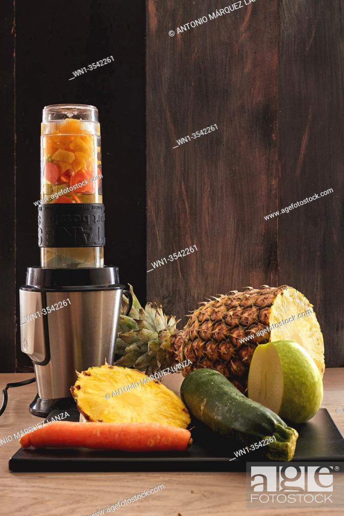 Stock Photo: veggie juicy made in a blender of pineapple, apple, cucumber and carrot in a dark background.