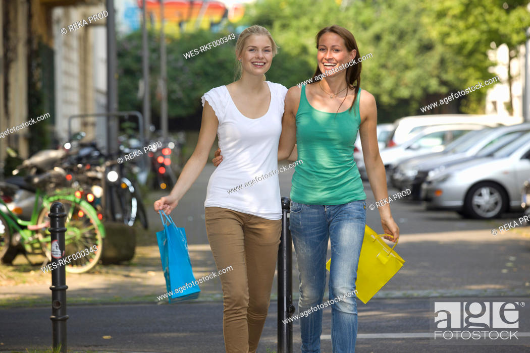 Stock Photo: Germany, North Rhine Westphalia, Cologne, Young women with shopping bags on street, smiling.