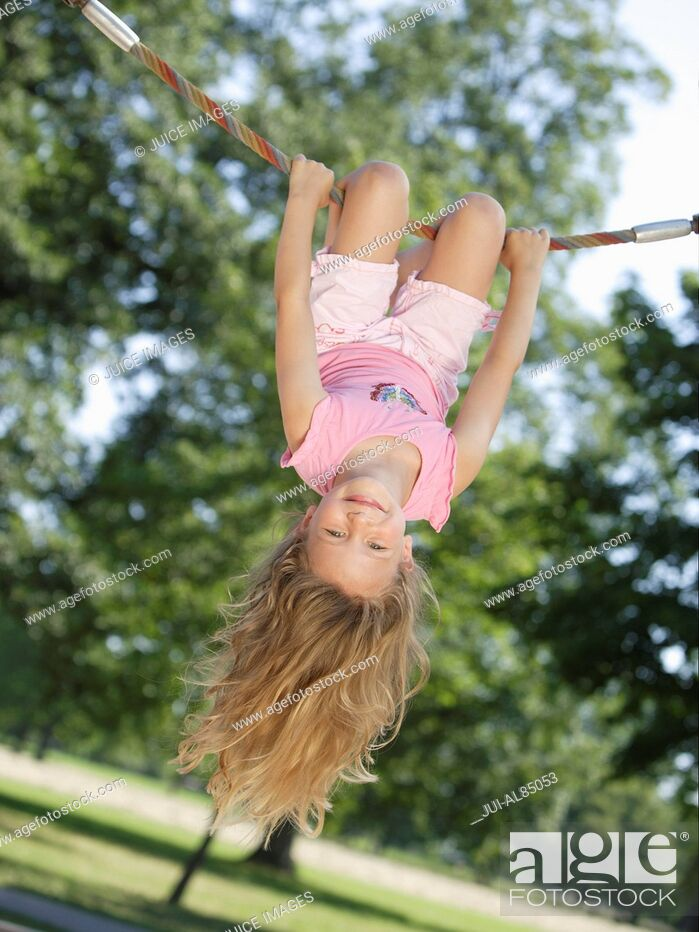 Stock Photo: Girl hanging upside down on rope at playground.