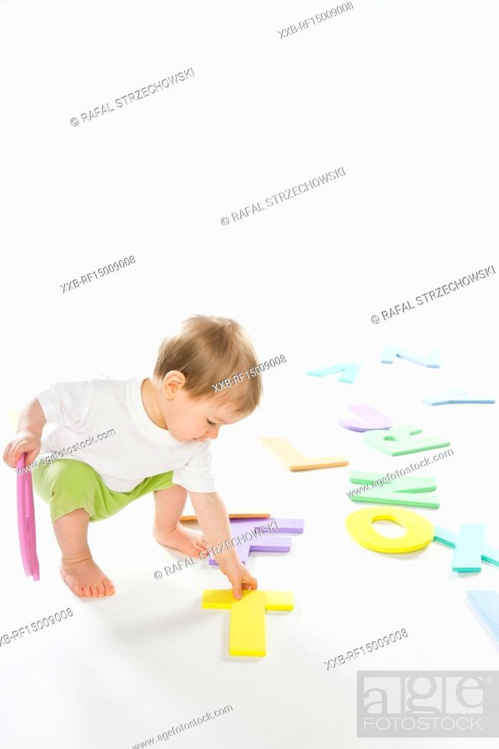 Stock Photo: baby boy playing with letters.