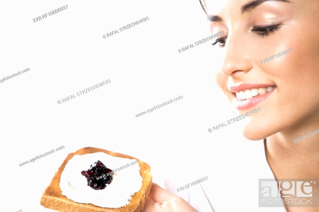 Stock Photo: Woman eating toast with cottage cheese and jam.