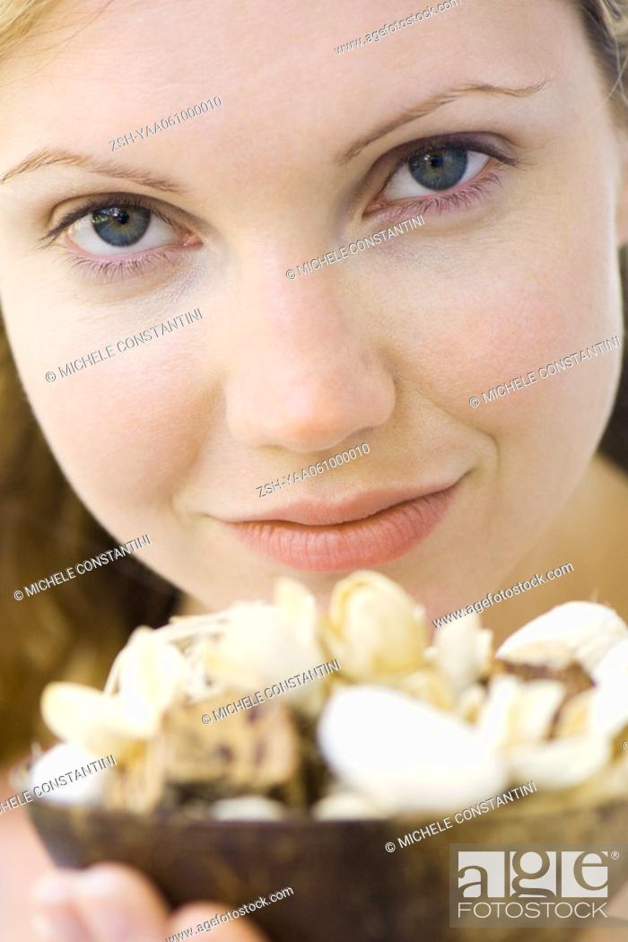 Stock Photo: Woman holding up bowl of flowers, smiling at camera, close-up.