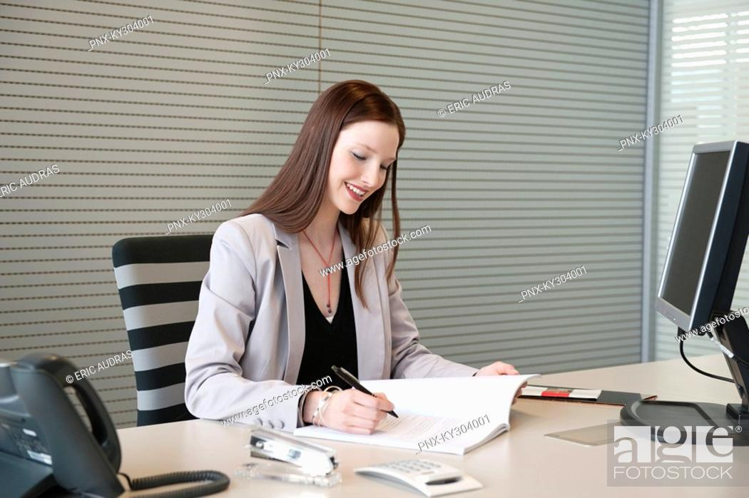 Stock Photo: Businesswoman doing paperwork in an office.