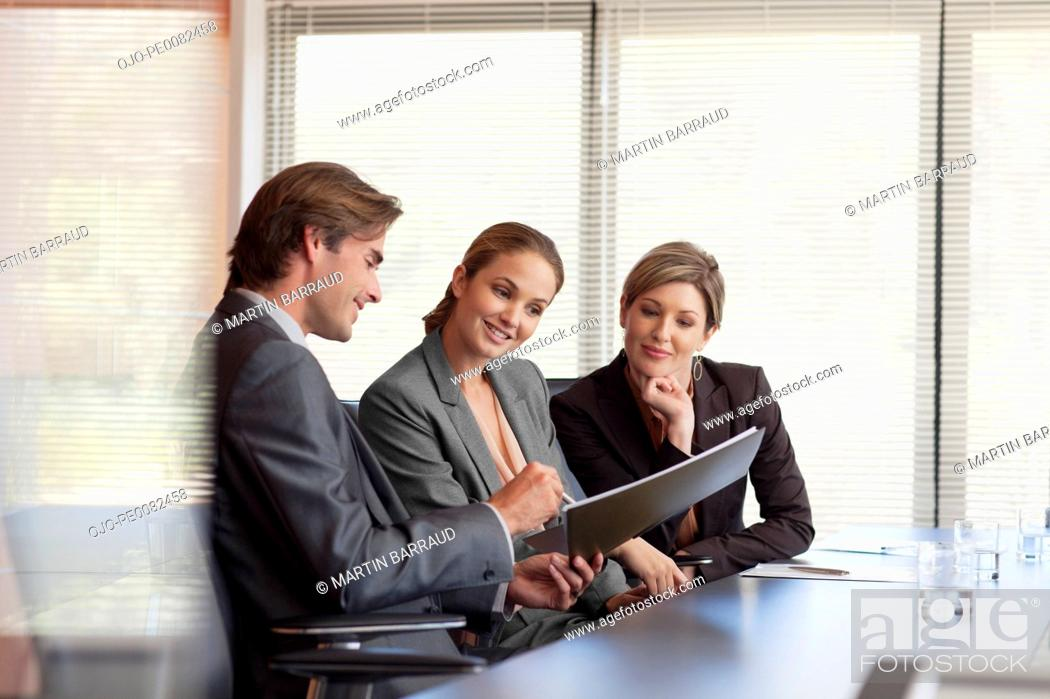 Stock Photo: Business people reviewing paperwork in conference room.