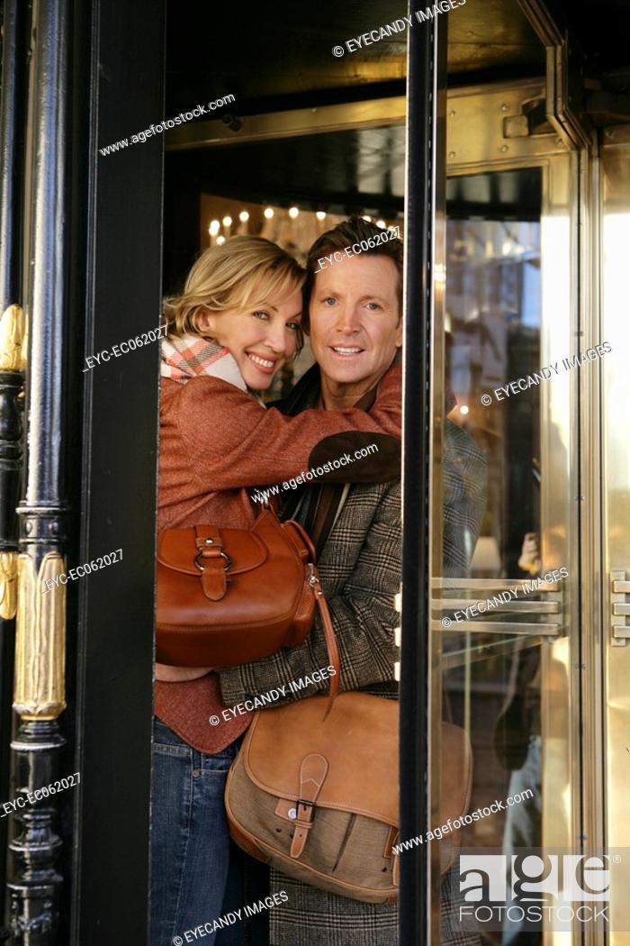 Stock Photo: Mature couple inside revolving doors.