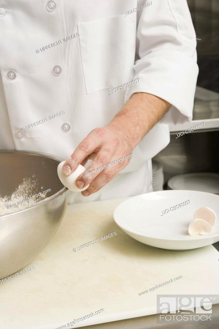 Stock Photo: Chef cracking egg on bowl.