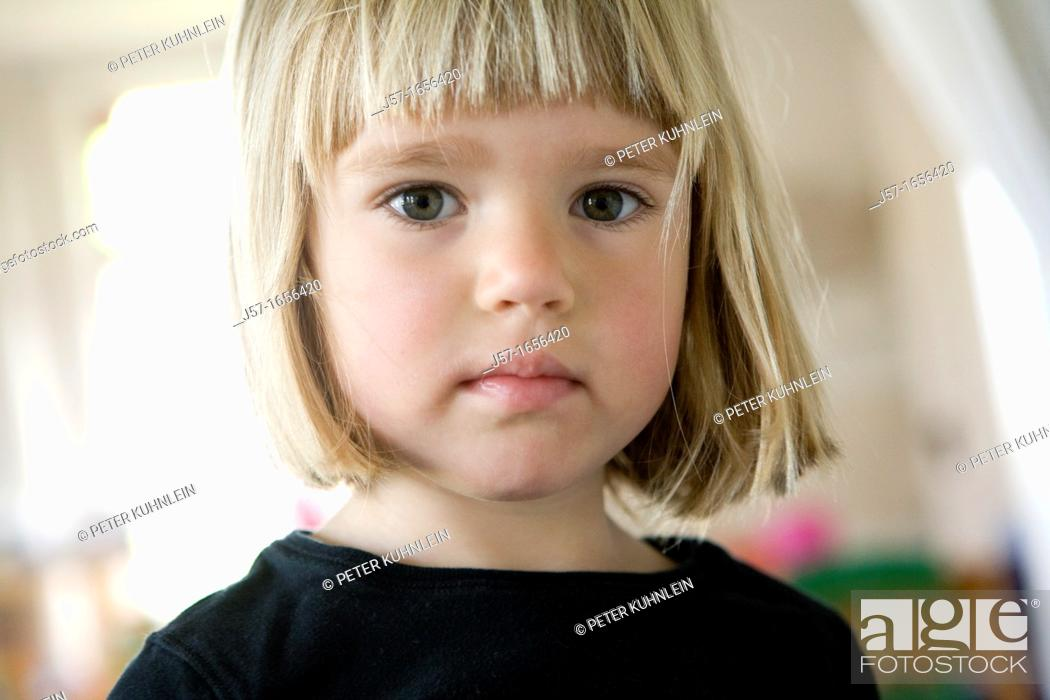 Stock Photo: Portrait of a 4 year old girl in a black shirt with blond straight hair looking engagingly into the camera.