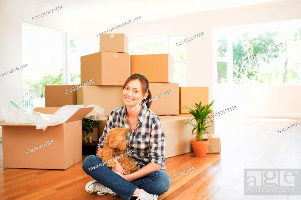 Stock Photo: Woman sitting on floor of new house with teddy bear.