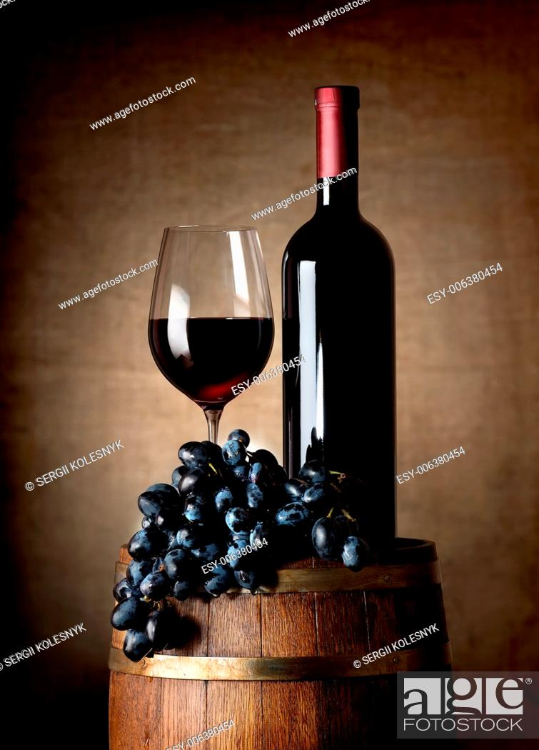 Stock Photo: Bottle of red wine, wine glass, grapes and wooden barrel.