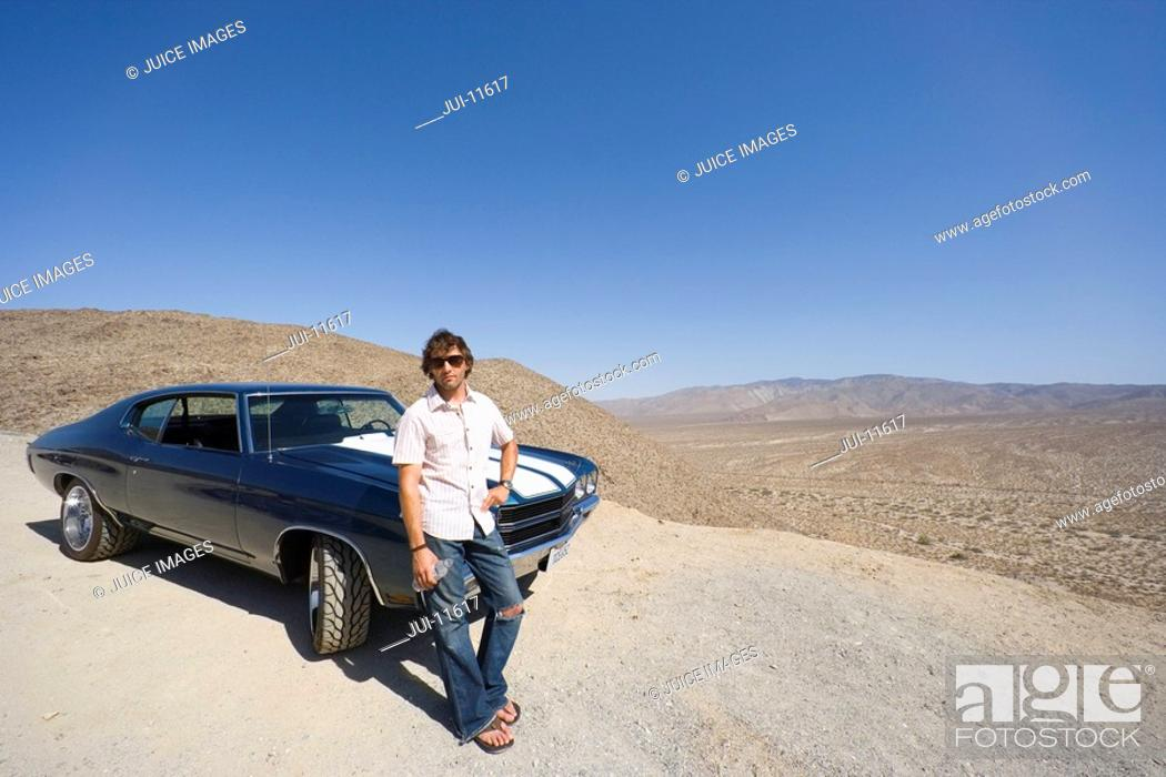 Stock Photo: Young man with water bottle in sunglasses by car in desert.