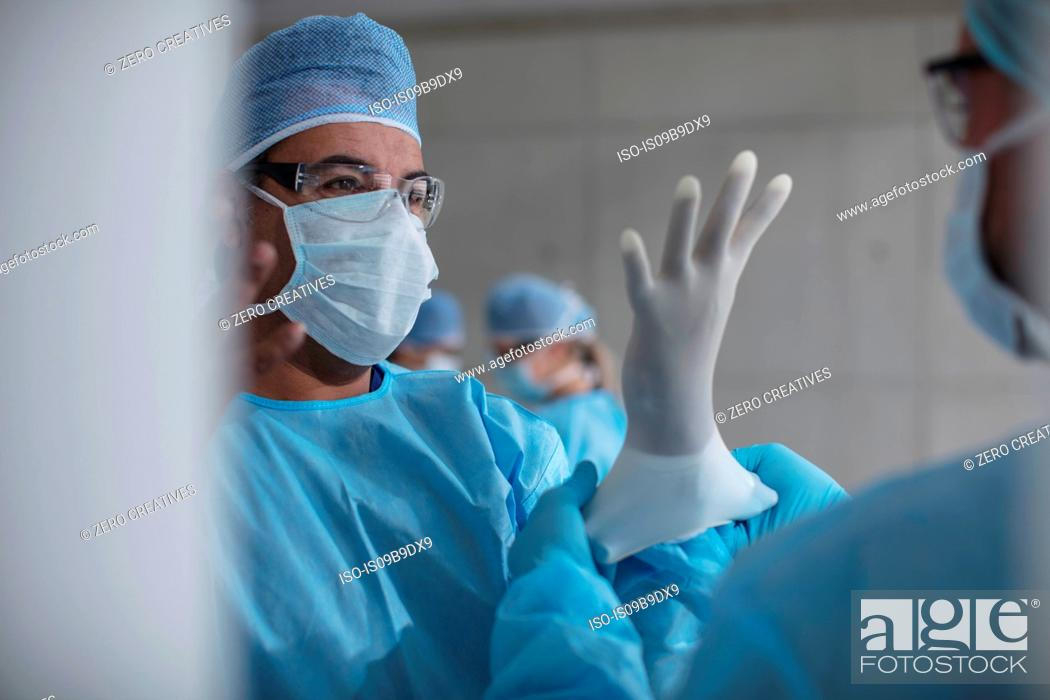 Stock Photo: Surgeons preparing for surgery, putting on latex gloves.