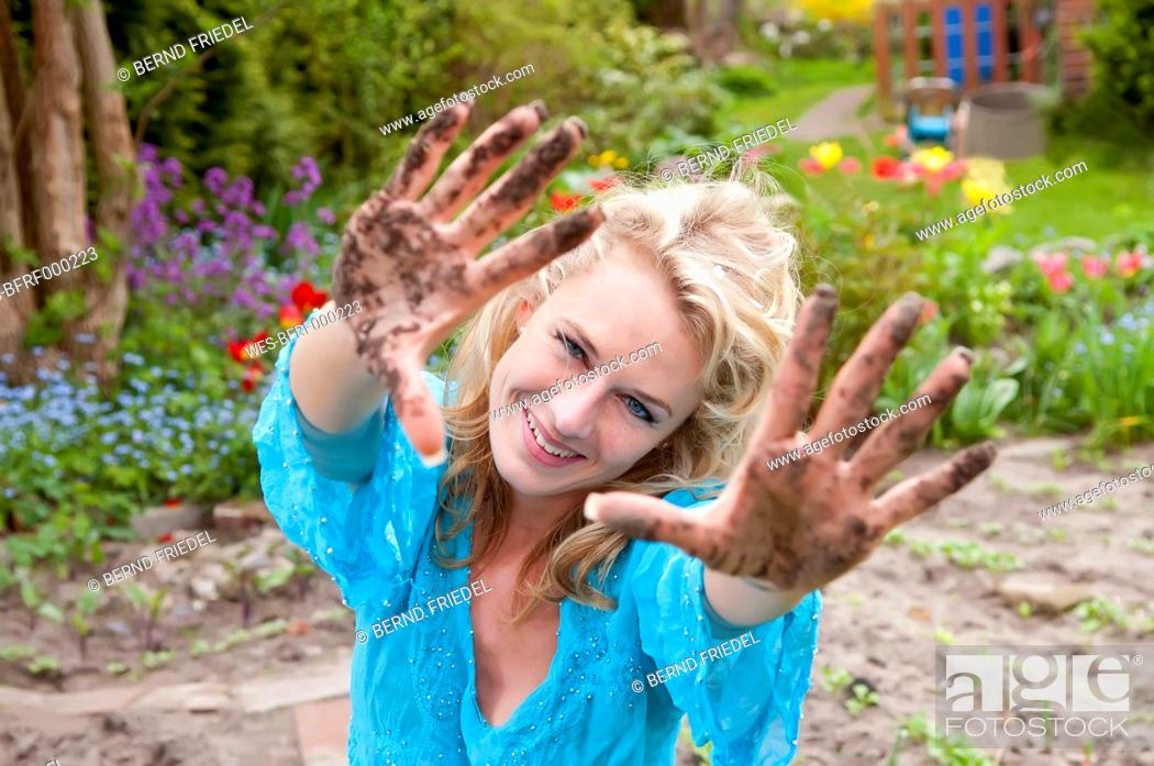 Stock Photo: Germany, Brandenburg, Portrait of mid adults woman with dirty hands in garden, smiling.