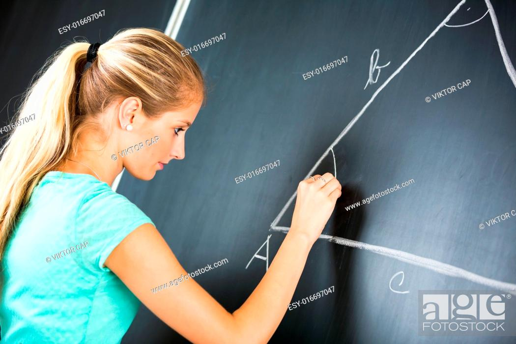 Stock Photo: Pretty young elementary school/college teacher writing on the chalkboard/blackboa rd during a math class (color toned image shallow DOF).