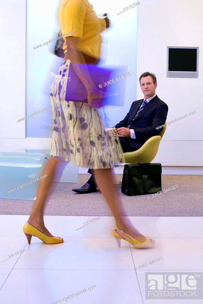 Stock Photo: Businessman watching businesswoman walking in foyer, low section blurred motion.