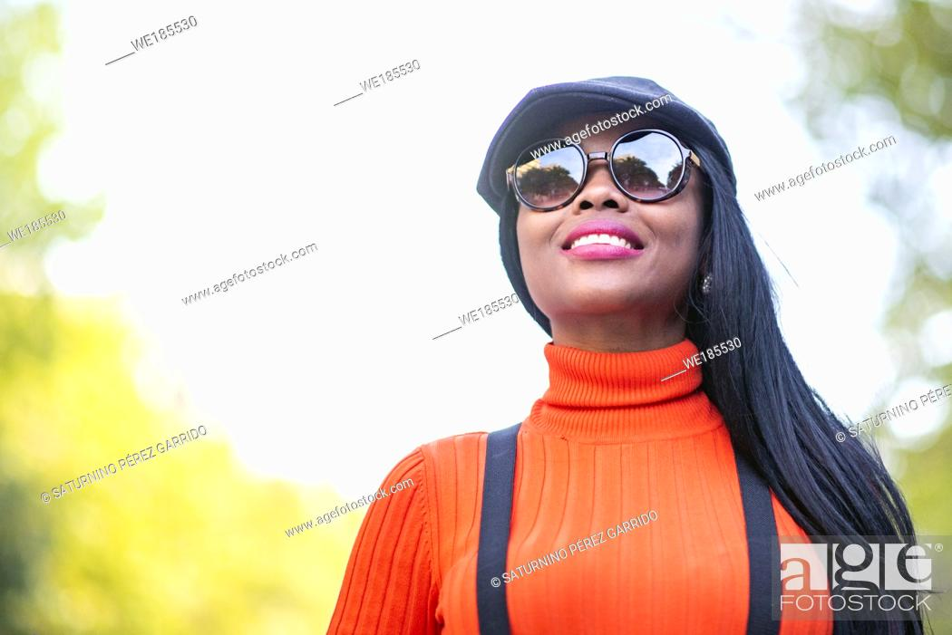 Stock Photo: Beautiful brown skinned woman with sunglasses and beautiful smile.