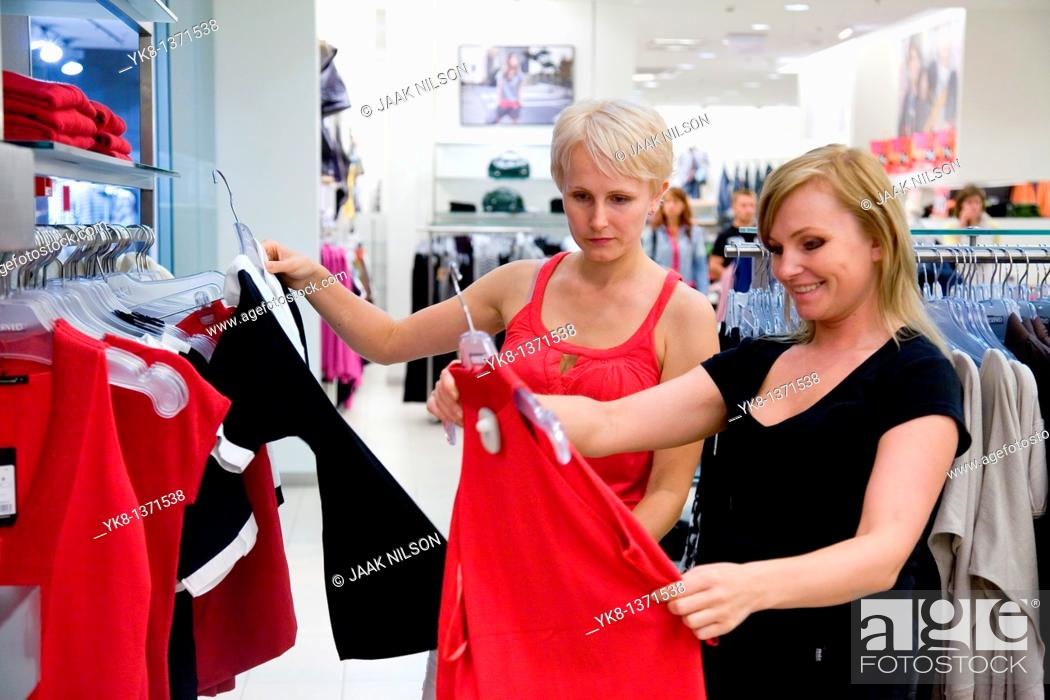 Stock Photo: Young women shopping and comparing different clothes in store.