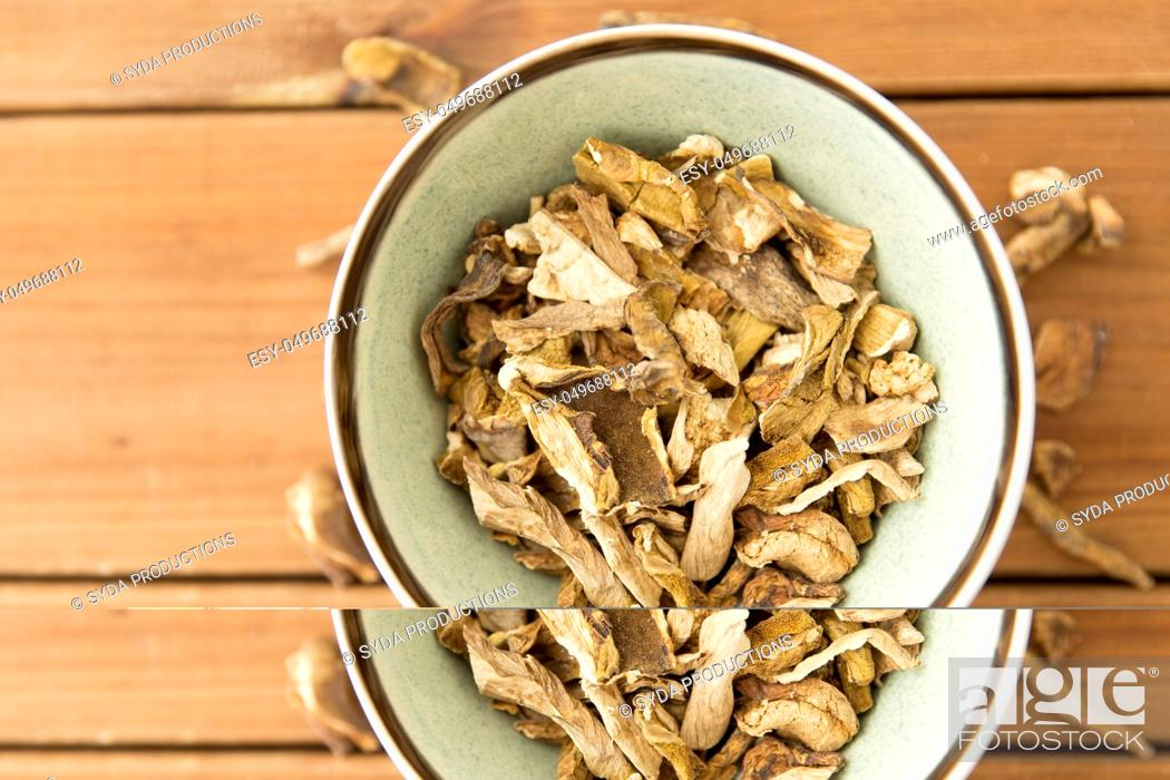 Stock Photo: dried mushrooms in bowl on wooden background.