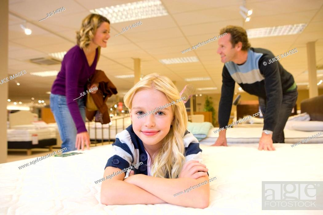 Stock Photo: Girl 6-8 on bed in furniture shop, parents in background, smiling, portrait.