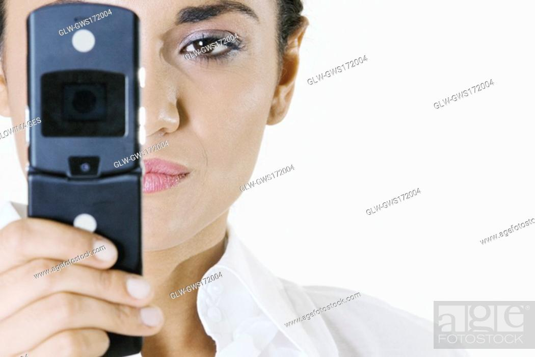 Stock Photo: Close-up of a young woman holding a mobile phone.