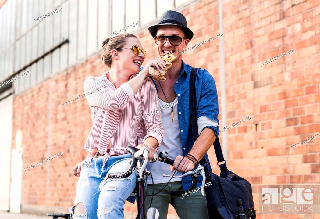Stock Photo: Happy young couple with bicycle sharing a snack.