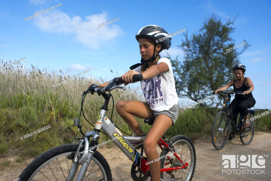 Photo de stock: Mother and daughter are riding in a bike. Pudent Lake. Formentera. Balearic Islands, Spain, Europe. Bicycle route.