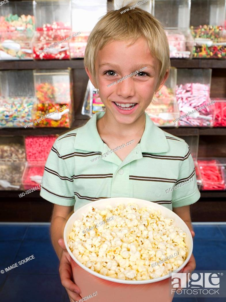Stock Photo: Portrait of a boy holding a tub of popcorn.