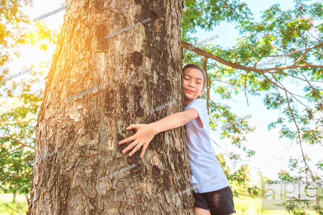 Stock Photo: girl hugging tree trunk in park.