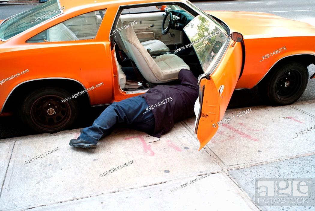 Stock Photo: Man fixing an old car.
